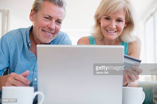 USA, New Jersey, Portrait of couple using laptop, with credit card in view
