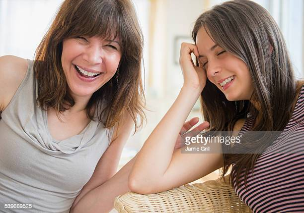 USA, New Jersey, Portrait of mom and teenage girl (14-15) laughing at home
