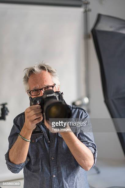 USA, New Jersey, Portrait of photographer in his studio taking shot