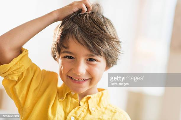 USA, New Jersey, Portrait of smiling boy (6-7) with hand in hair