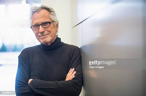 usa, new jersey, portrait of smiling senior man standing in office corridor - turtleneck stock pictures, royalty-free photos & images