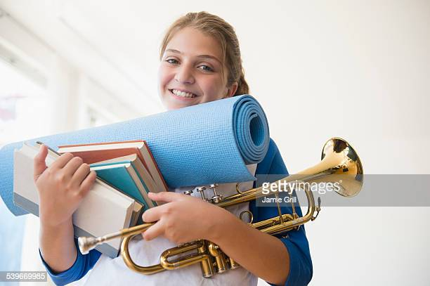 USA, New Jersey, Portrait of teenage girl (12-13) holding rolled-up exercise mat, books, and trumpet