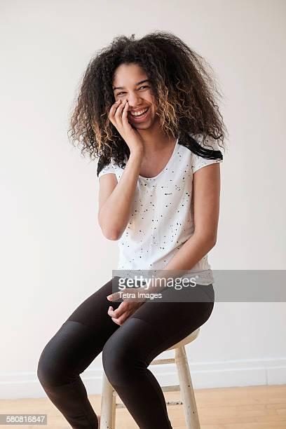 USA, New Jersey, Portrait of teenage girl (16-17) sitting on stool