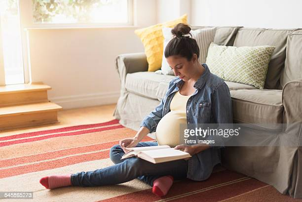 usa, new jersey, pregnant woman sitting on floor reading book - topknot stock pictures, royalty-free photos & images