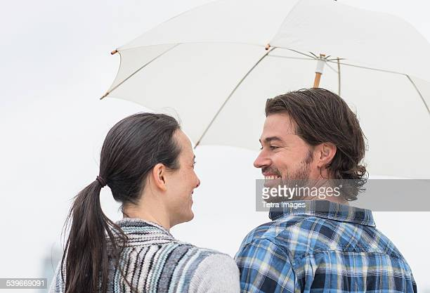 USA, New Jersey, Rear view of couple under umbrella