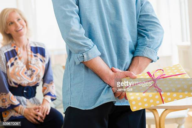 usa, new jersey, rear view of man holding wrapped birthday present behind back standing before smiling woman - anniversary stock pictures, royalty-free photos & images