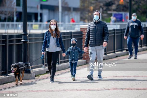New Jersey residents walk their dog while wearing masks due to the coronavirus outbreak on April 19 2020 in West New York New Jersey COVID19 has...