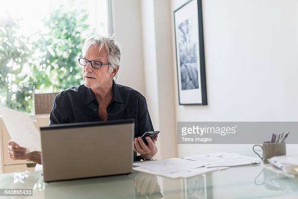 USA, New Jersey, Senior man sitting in home office and using laptop