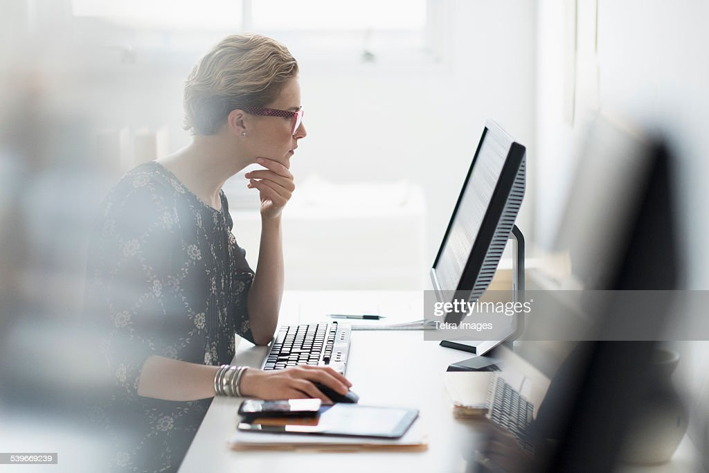 USA, New Jersey, Side view of business woman working on desktop pc in office : Stock Photo