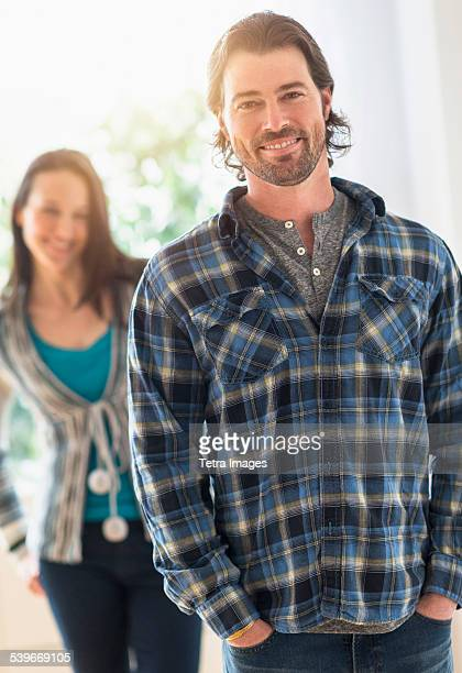 USA, New Jersey, Smiling man looking at camera, woman in background