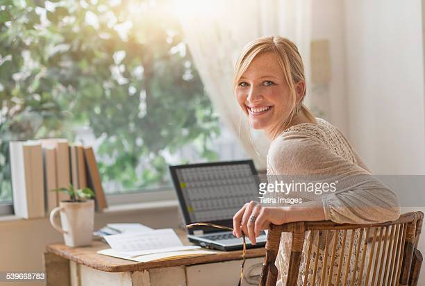 usa, new jersey, smiling woman sitting at desk and looking over shoulder  - looking over shoulder stock pictures, royalty-free photos & images