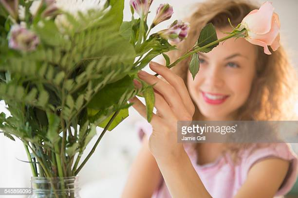 USA, New Jersey, Smiling young woman putting flowers in vase