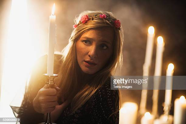 USA, New Jersey, Sorceress holding candle in dark room