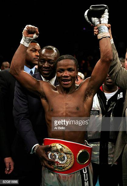 New Jersey State Athletic Commissioner Larry Hazard holds the belt on Kassim Ouma after he won his bout against Kofi Jantuah by unanimous decision...