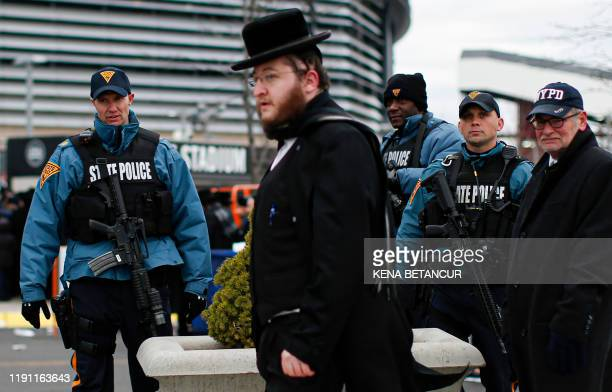 New Jersey State Police officers stand guard as people congregate at the MetLife Stadium to celebrate Siyum HaShas the completion of the reading of...