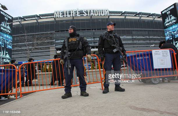 New Jersey State Police officers stand guard in front of MetLife Stadium on January 1 in East Rutherford New Jersey as people arrive for an event...
