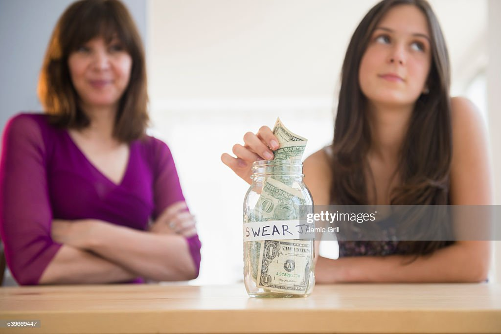 USA, New Jersey, Teenage girl (14-15) putting money in swear jar : Stock Photo