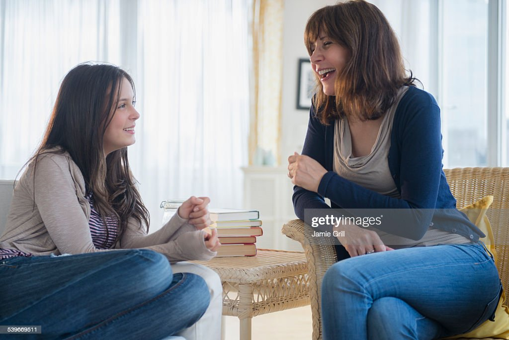 USA, New Jersey, Teenage girl (14-15) talking with her mom in living room : Stock Photo