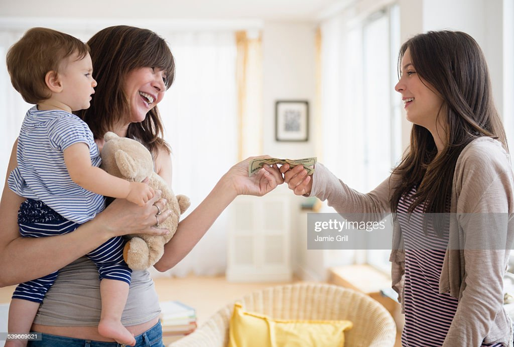 USA, New Jersey, Woman paying teenage nanny (14-15) for taking care of her son (12-17 months) : ストックフォト