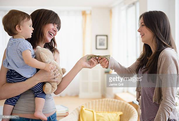 usa, new jersey, woman paying teenage nanny (14-15) for taking care of her son (12-17 months) - nanny stock photos and pictures