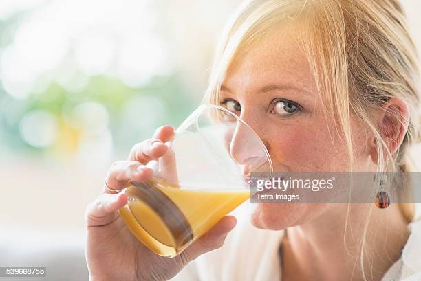 USA, New Jersey, Woman sitting in living room and drinking orange juice