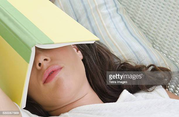 USA, New Jersey, Woman sleeping with book on face