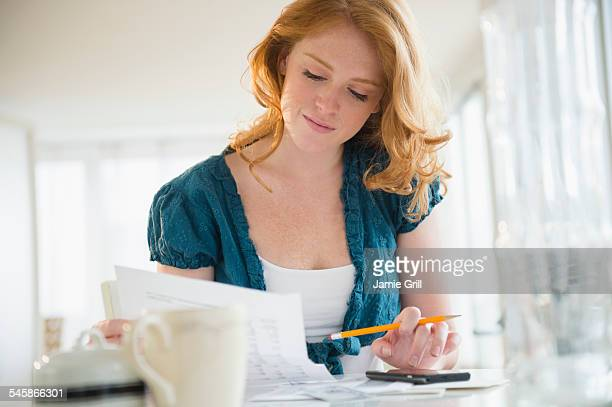 USA, New Jersey, Young woman doing paperwork at home