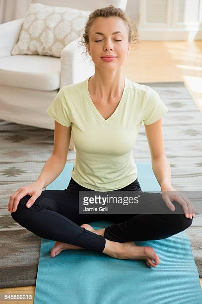 USA, New Jersey, Young woman doing yoga in living room