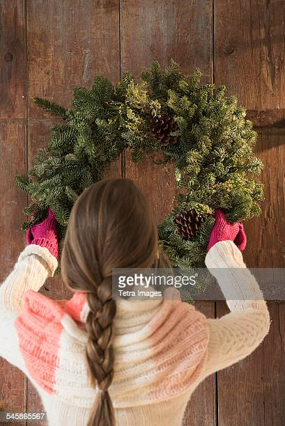 USA, New Jersey, Young woman hanging christmas wreath on door