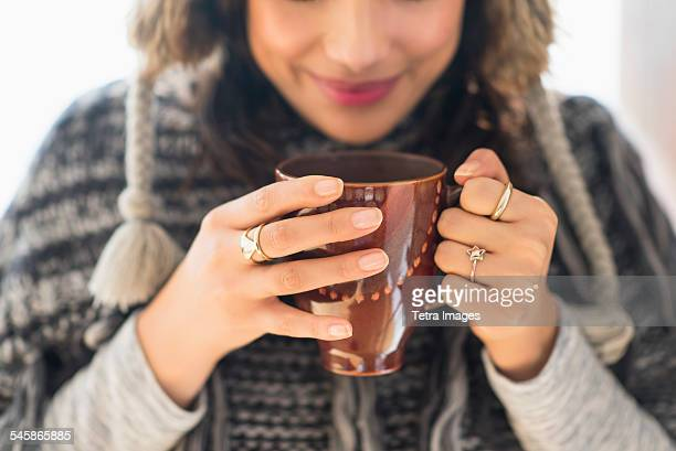 usa, new jersey, young woman holding mug with hot drink - woman cradling mug stock pictures, royalty-free photos & images