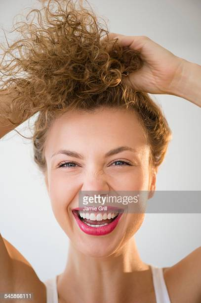 USA, New Jersey, Young woman laughing and holding hair up