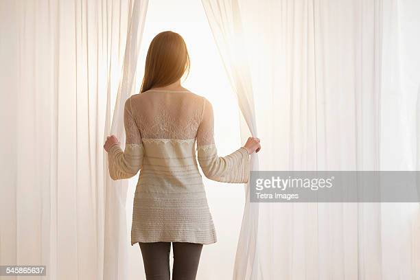 USA, New Jersey, Young woman opening curtains in morning