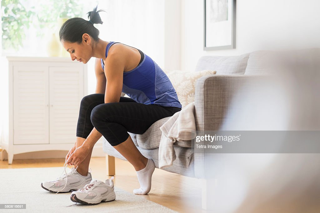 USA, New Jersey, Young woman putting on shoes : Stock Photo