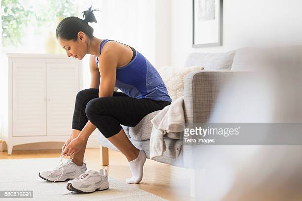 USA, New Jersey, Young woman putting on shoes
