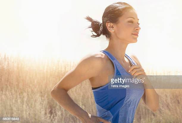 USA, New Jersey, Young woman running outdoors