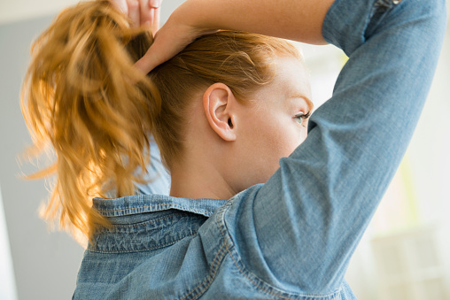 USA, New Jersey, Young woman tying hair - gettyimageskorea