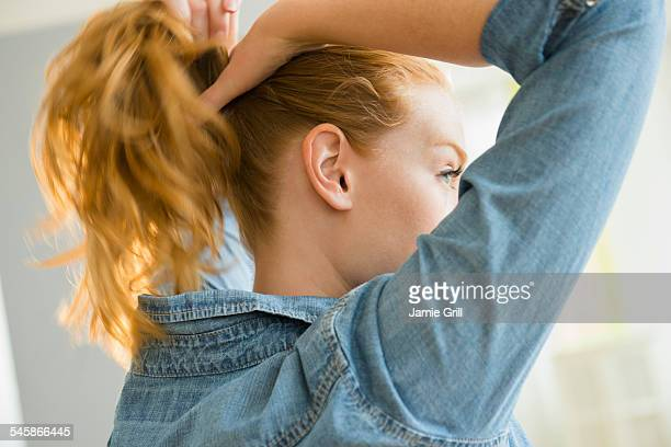 usa, new jersey, young woman tying hair - ponytail stock pictures, royalty-free photos & images