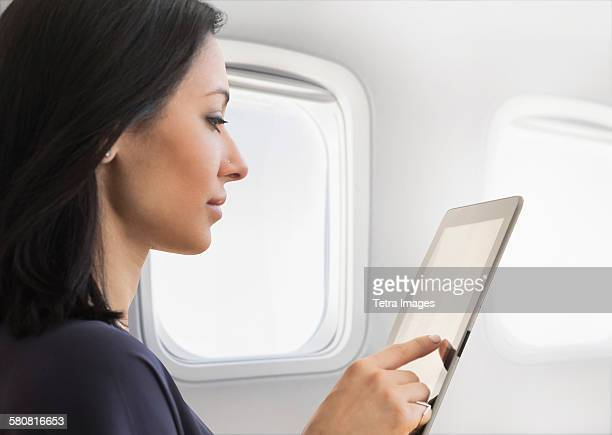 USA, New Jersey, Young woman using tablet on plane