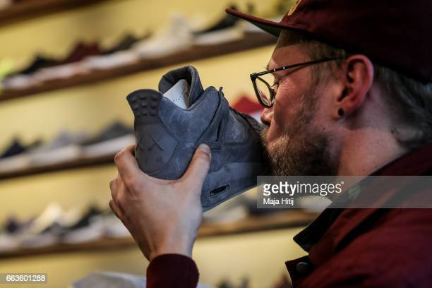 New KAWS x Air Jordan IV sneakers buyer kisses his shoe during the sale at 'Overkill' sneakers store on March 31 2017 in Berlin Germany Several dozen...