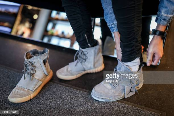 "New KAWS x Air Jordan IV sneakers buyer tries the shoe during the sale at ""Overkill"" sneakers store on March 31, 2017 in Berlin, Germany. Several..."
