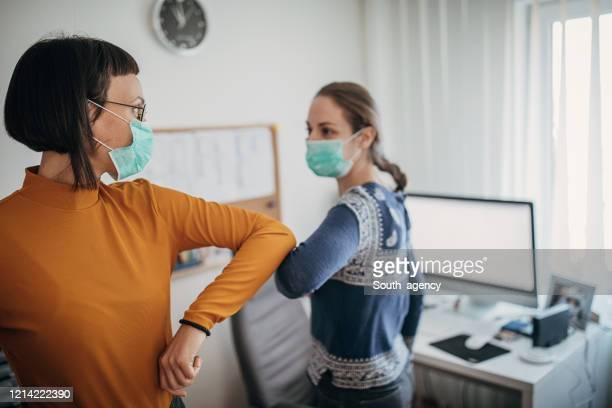 new kind of greeting with elbows do to coronavirus outbreak - questão social imagens e fotografias de stock