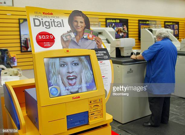 A new Kodak photo kiosk used to print pictures from a digital camera sits in the foreground while a photo technician works on a film processor...