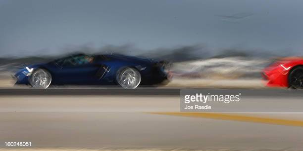 New Lamborghini Aventador LP7004 Roadsters are seen using a slow shutter speed as they are driven along the south runway at the Miami International...
