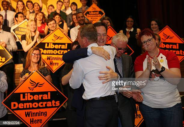 New Liberal Democrat Party Leader Tim Farron hugs former leader of the party Nick Clegg applauds as contender for the leadership, Norman Lamb stands...