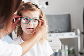 New look. Doctor giving the child new glasses for her vision