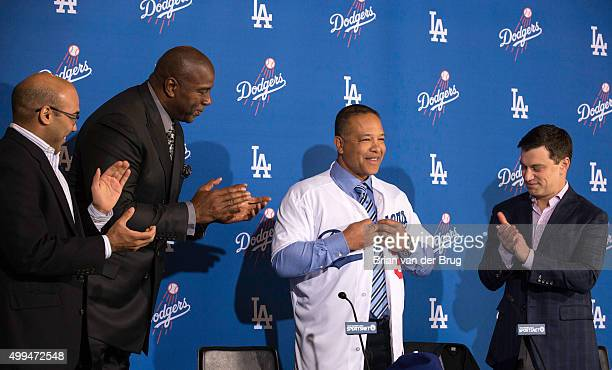 New Los Angeles Dodgers manager Dave Roberts tries on his new jersey as General Manager Farhan Zaidi left Magic Johnson and President of Baseball...