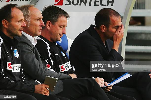 New manager Andreas Mueller assistant coach Rainer Widmayer and head coach Markus Babbel of Hoffenheim sits on the bench prior to the Bundesliga...