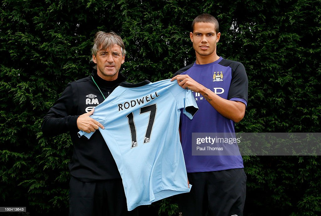 New Manchester City player Jack Rodwell (R) and manager manager Roberto Mancini pose for a photograph at the MCFC Carrington Training Complex on August 17, 2012 in Manchester, England.
