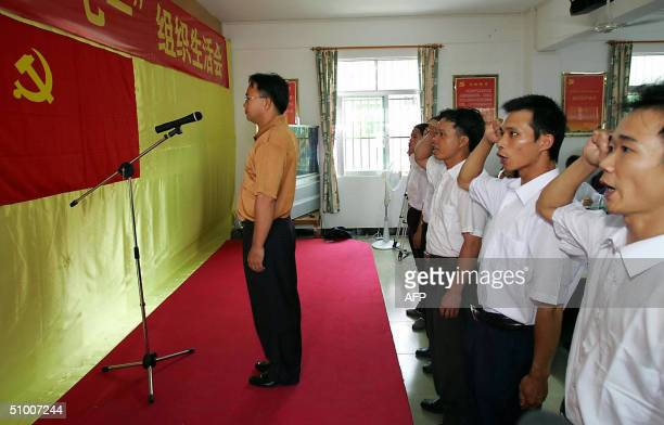 New members of the Chinese Communist Party pledge their allegiance before the party flag during a ceremony to admit the new recruits into the CCP in...