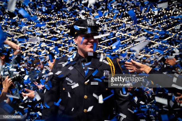 New members of the New York City Police Department embrace at the conclusion of their police academy graduation ceremony at the Theater at Madison...
